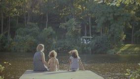 放松在木码头的可爱的家庭由池塘 影视素材