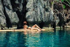 放松在木筏的美丽的妇女在热带盐水湖 免版税库存图片