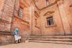 放松在果阿的历史大教堂石台阶的美丽的妇女,建造在17世纪 免版税库存照片