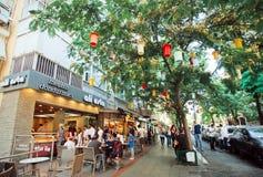 放松在树树荫下的人们临近室外咖啡馆 免版税库存图片
