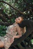 放松在树的美丽的女孩 免版税库存图片