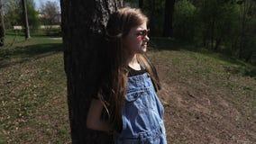 放松在树附近的女孩女孩在公园 股票录像