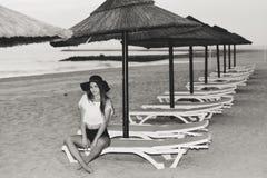 放松在椅子休息室,夏天户外背景的晚上的海滩的年轻俏丽的夫人 库存照片