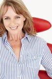 放松在椅子的中间年龄女实业家 免版税库存图片