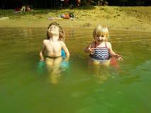 放松在椅子的兄弟和姐妹在水中 图库摄影