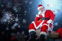 放松在椅子的圣诞老人的综合图象 库存照片