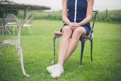放松在椅子的妇女在庭院里 免版税库存照片