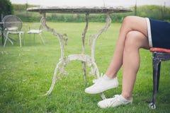 放松在椅子的妇女在庭院里 库存照片
