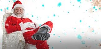 放松在椅子的快乐的圣诞老人的综合图象 免版税图库摄影