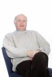 放松在椅子的愉快的老人 免版税库存图片