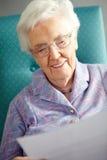 放松在椅子读取信函的高级妇女 免版税库存图片