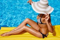 放松在比基尼泳装和帽子的美丽的被晒黑的妇女画象在游泳场 胶凝体波兰红色修指甲 热夏日和明亮 库存图片