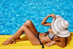 放松在比基尼泳装和帽子的美丽的被晒黑的妇女画象在游泳场 胶凝体波兰红色修指甲 热夏日和明亮 免版税库存照片
