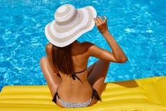 放松在比基尼泳装和帽子的美丽的被晒黑的妇女画象在游泳场 胶凝体波兰红色修指甲 热夏日和明亮 库存照片