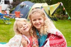 放松在毯子的两个女孩在家庭野营假日期间 免版税库存图片