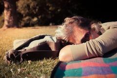 放松在毯子的妇女在日落 免版税库存图片