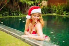 放松在水池的圣诞老人帽子的妇女 库存照片