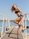 放松在水背景的黑泳装的美丽的白肤金发的女孩 游泳时尚概念 免版税库存照片