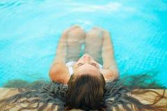 放松在池的妇女。 背面图 免版税库存图片