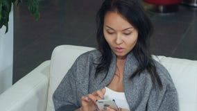 放松在沙发和使用智能手机的逗人喜爱的亚裔妇女 免版税库存照片