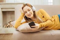 放松在沙发和听到音乐的微笑的妇女 免版税库存图片