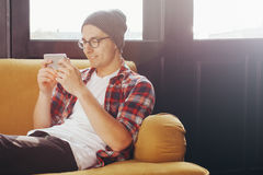 放松在沙发和看他巧妙的电话的年轻人 免版税库存照片