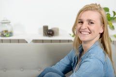 放松在沙发的一名美丽的年轻白肤金发的妇女 免版税图库摄影