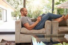放松在沙发的人使用片剂个人计算机 库存图片