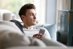 放松在沙发的人拿着手机 免版税图库摄影