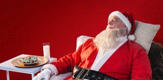 放松在沙发的圣诞老人的综合图象 免版税图库摄影