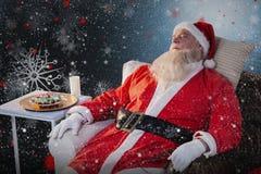 放松在沙发的圣诞老人的综合图象 免版税库存照片