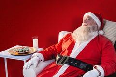 放松在沙发的圣诞老人的综合图象 库存图片