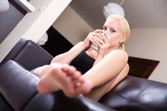 放松在沙发的女孩喝一杯咖啡 免版税库存图片