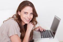 放松在沙发的妇女使用膝上型计算机 免版税库存图片