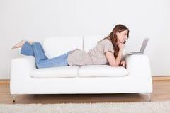 放松在沙发的妇女使用膝上型计算机 库存照片