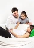 放松在沙发的年轻人怀孕的系列 免版税库存图片