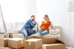 放松在沙发的微笑的夫妇在新的家 免版税库存照片