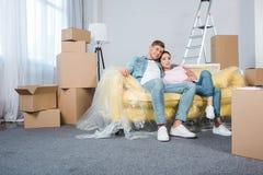 放松在沙发的愉快的年轻夫妇,当搬入时 免版税库存图片