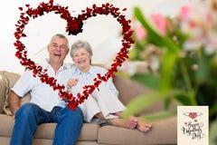 放松在沙发的愉快的资深夫妇的综合图象 免版税库存照片