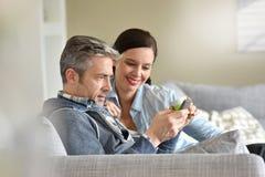 放松在沙发的成熟夫妇 免版税图库摄影