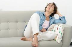 放松在沙发的成熟妇女 图库摄影