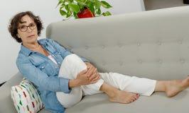 放松在沙发的成熟妇女 库存照片