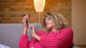 放松在沙发的桃红色毛线衣的特写镜头射击白肤金发的主妇冲浪在舒适家庭环境的智能手机 影视素材