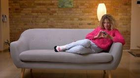 放松在沙发的桃红色毛线衣的白肤金发的主妇冲浪网使用在舒适家庭环境的智能手机 股票录像