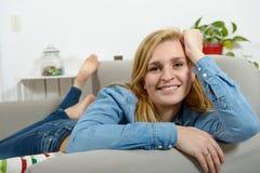 放松在沙发的美丽的年轻白肤金发的妇女 库存图片