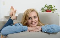 放松在沙发的美丽的年轻白肤金发的妇女 免版税图库摄影