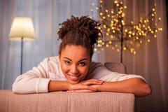 放松在沙发的逗人喜爱的少妇 免版税库存照片