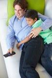 放松在沙发的顶上的观点的父亲和儿子看电视 库存图片