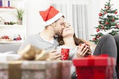 放松在沙发的年轻圣诞节夫妇 库存图片
