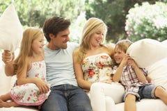 放松在沙发的年轻家庭画象 免版税图库摄影